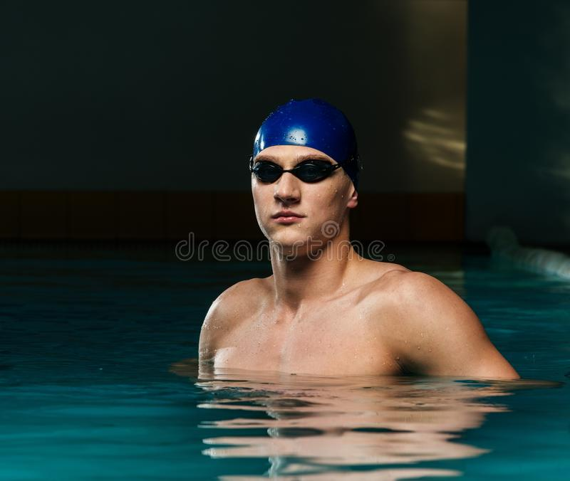Man in swimming pool. Muscular young man in blue cap in swimming pool stock photography