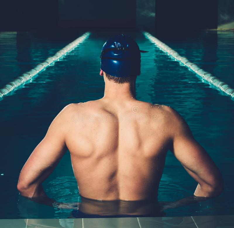 Man in swimming pool. Muscular young man in blue cap in swimming pool stock images