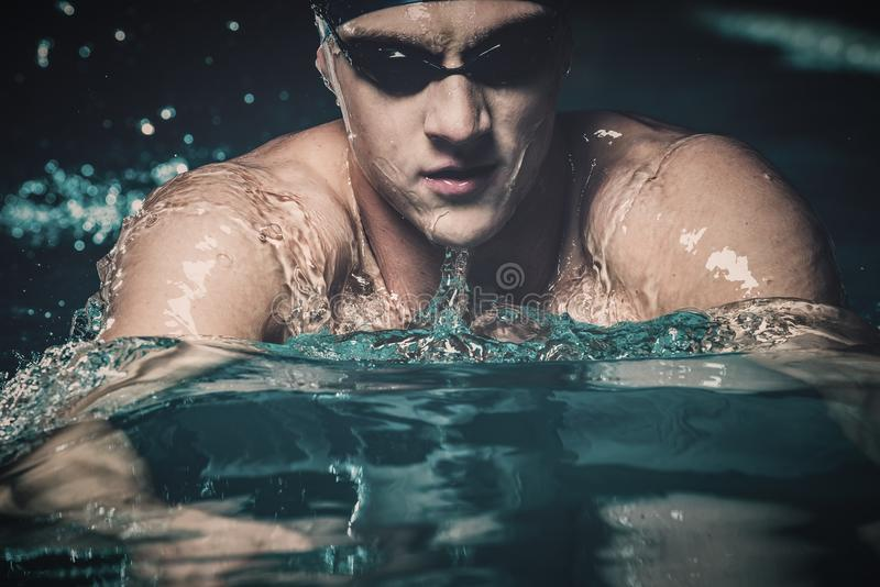 Man in swimming pool. Muscular young man in blue cap in swimming pool stock photos