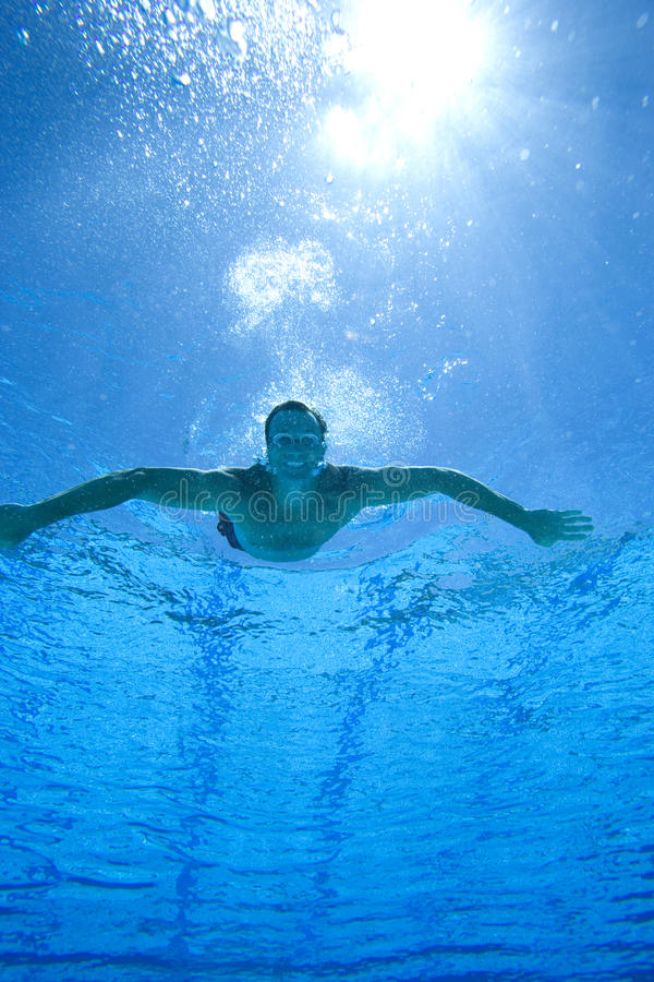 Man in swimming pool, portrait, underwater view (lens flare) royalty free stock images
