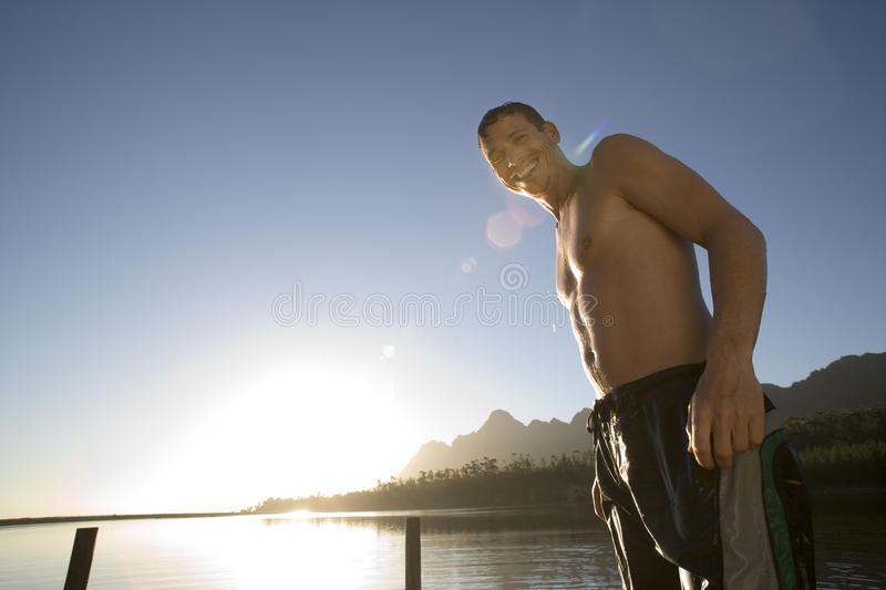 Man, in swimming shorts, standing on lake jetty at sunset, smiling, portrait, low angle view (lens flare, backlit) stock images