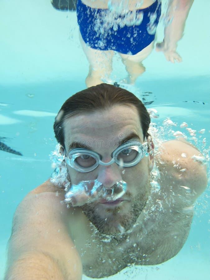 Man Swimming Underwater Stock Photo