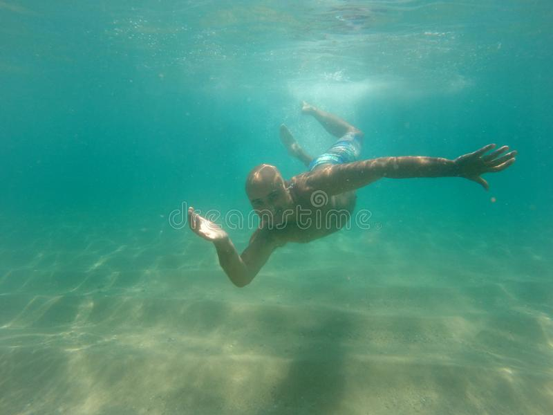 Man swimming underwater in the sea stock photo