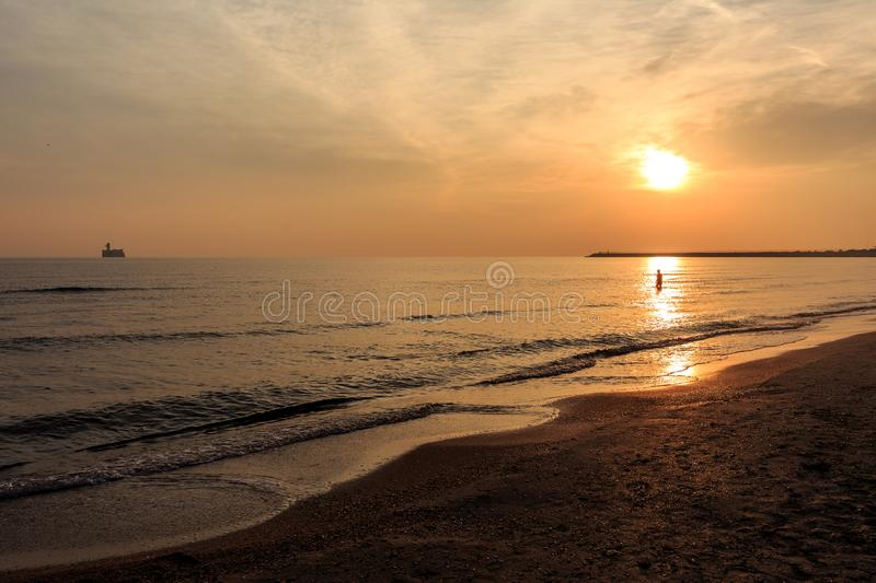 Man swims at sunrise, rising sun and clouds. Man swims at sunrise in the sea royalty free stock photos
