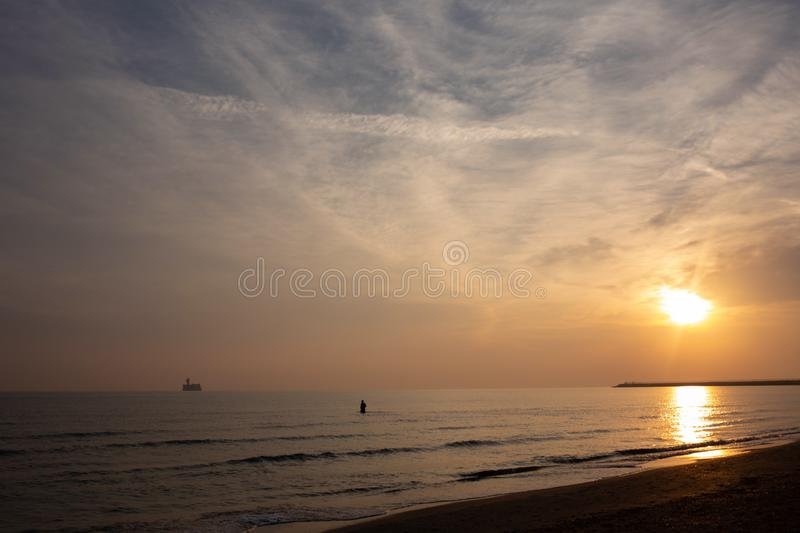 Man swims at sunrise, rising sun and clouds. Man swims at sunrise in the sea royalty free stock image
