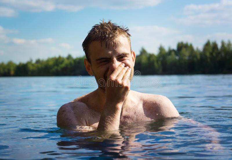 A man swims in the water of a lake, enjoys resting in the water, having fun royalty free stock photos