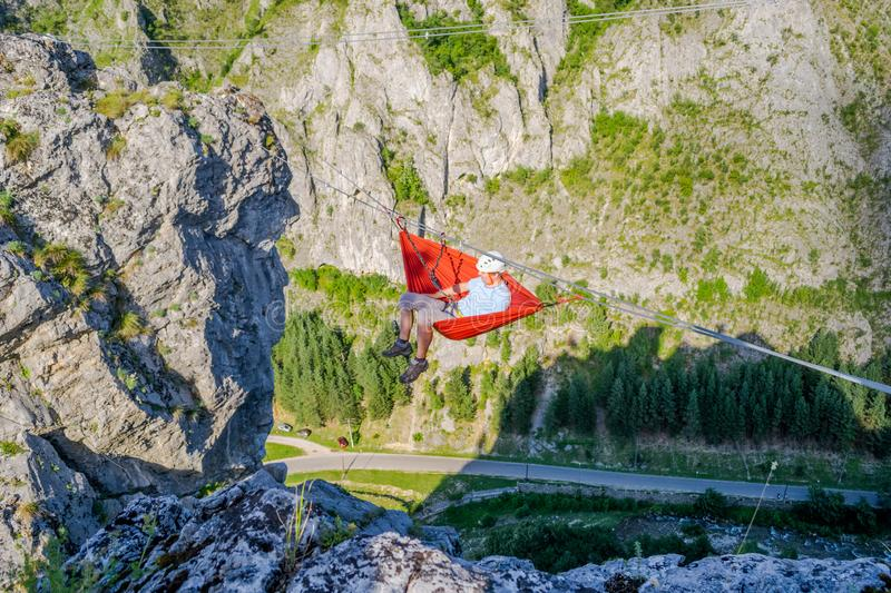 Man swinging in a hammock set up high in the air, between two mountain ridges stock photography