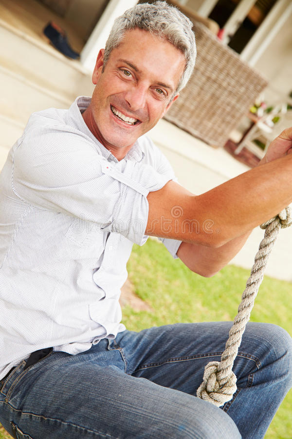 Man swinging at a playground, portrait royalty free stock photography