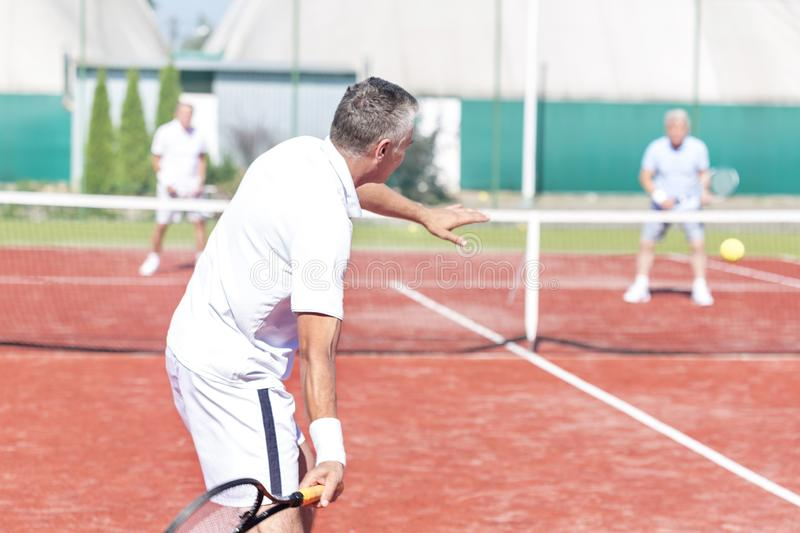 Man swinging racket while playing tennis doubles on red court during summer weekend royalty free stock photography