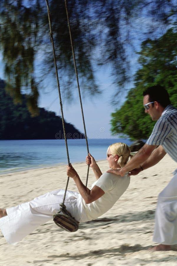 Man swinging woman on swing at beach royalty free stock photo