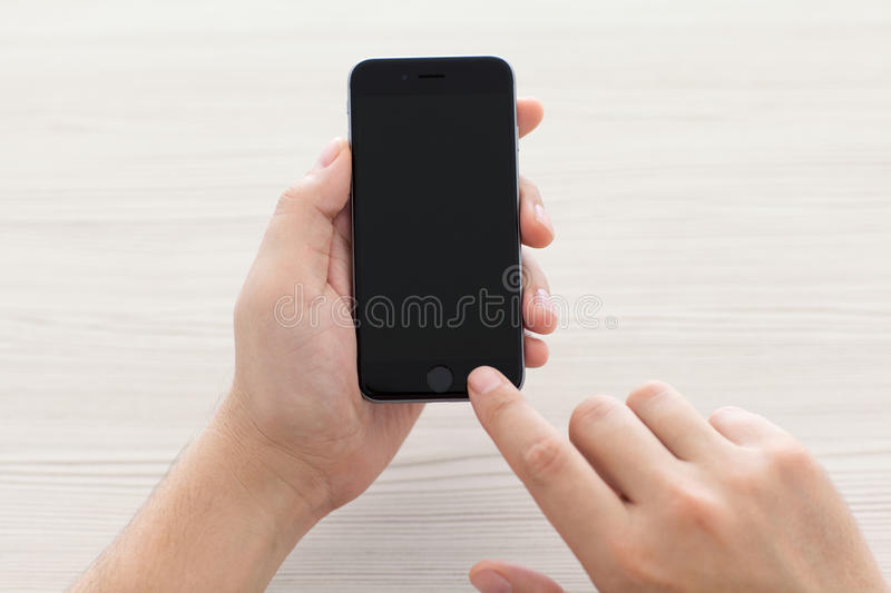 Man switch on the new iPhone 6 Space Gray holding it over the ta. Alushta, Russia - October 23, 2014: Man switch on the new iPhone 6 Space Gray holding it over stock image