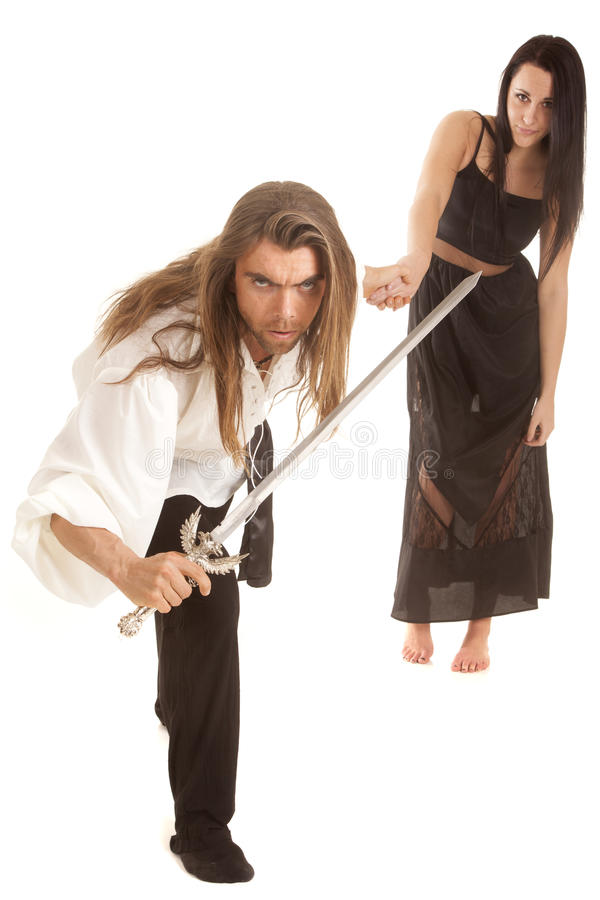 Man with sword leading woman in black royalty free stock photography