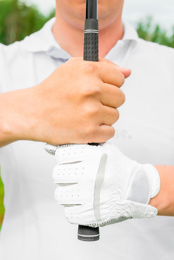 Man in a T-shirt holds a putter in front of him. A man in a T-shirt holds a putter in front of him royalty free stock photography