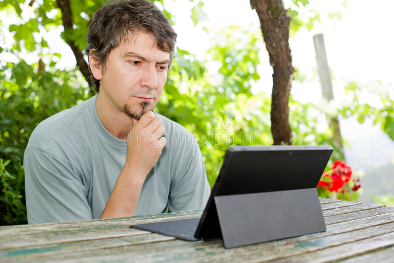 Man with tablet. Casual man working with a tablet pc, outdoor royalty free stock images