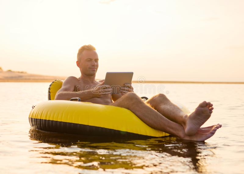 Man with a tablet on inflatable ring in the water at sunset stock photos