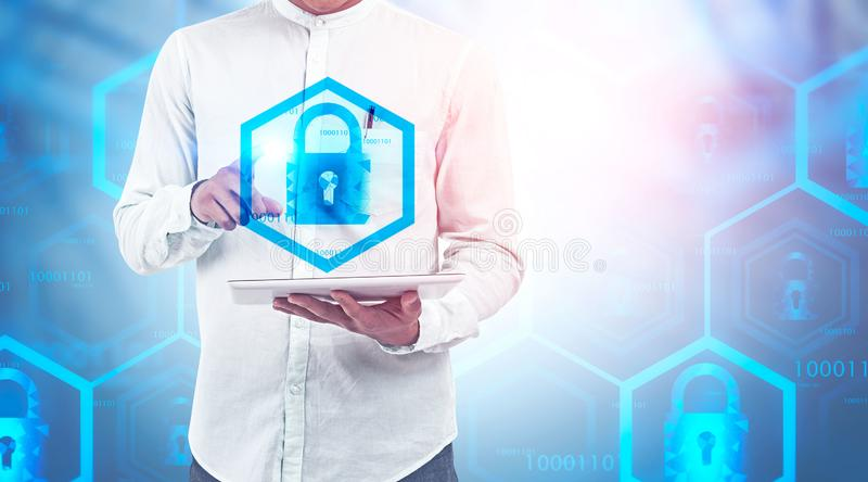 Man with tablet, online security concept. Man in white shirt using tablet computer with double exposure of online security interface. Concept of data protection royalty free stock photography