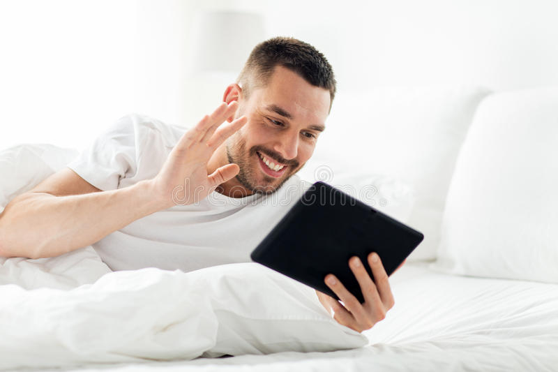 Man with tablet pc having video call in bed stock photography