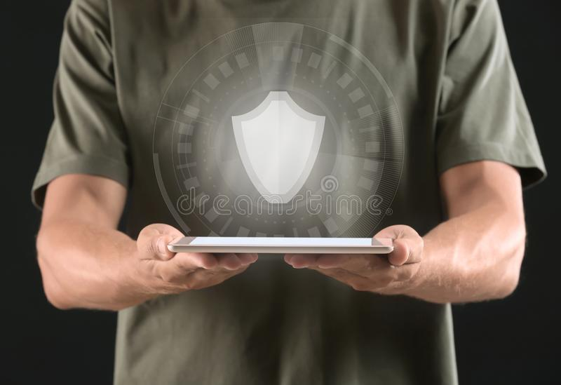 Man with tablet PC and shield icon on dark background. Data security concept stock photo