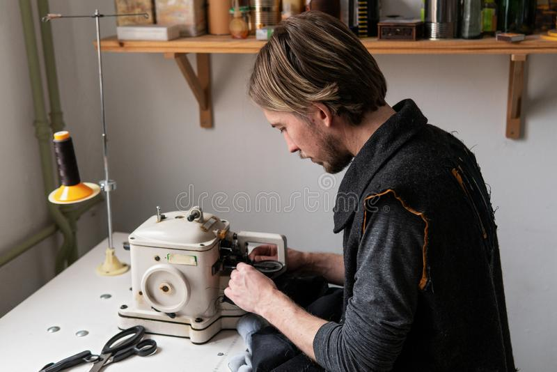 Man tailor working on furrier machine in workshop. Young man tailor working on furrier machine in workshop stock image