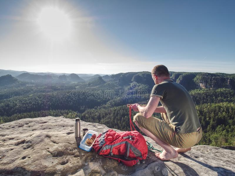 Man take break for snack while climbing in rocks. Hiker in shorts. And blue jersey stay barefoot on sandstone cliff, water, bottle, thermos, sports, equipment stock image