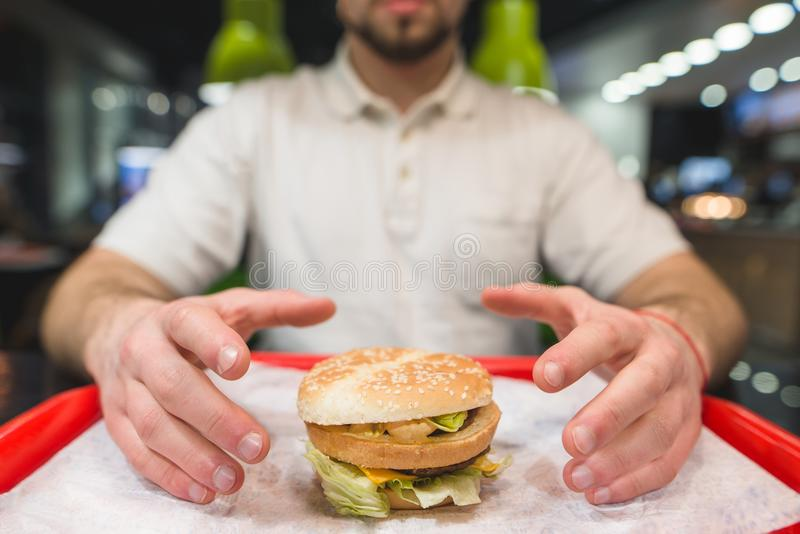 A man takes a large burger who is standing on the tray. Hands are drawn to the tasty cheeseburger. Focus on the burger. stock image