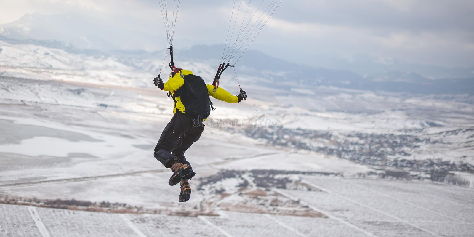 Man takes off with the speedglider from the mountain. royalty free stock image