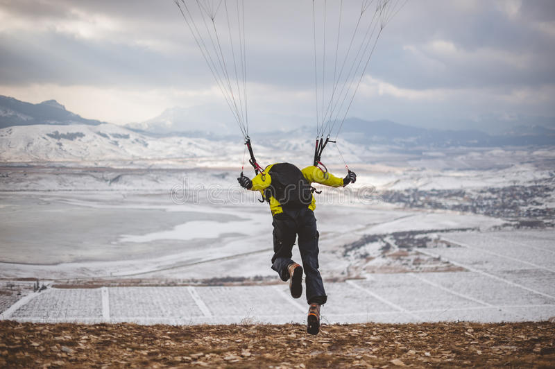 Man takes off with the speedglider from the mountain. stock photos