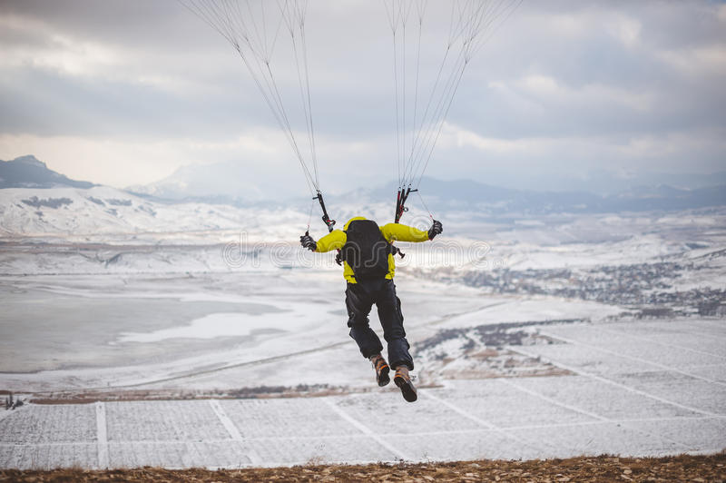 Man takes off with the speedglider from the mountain. royalty free stock photography