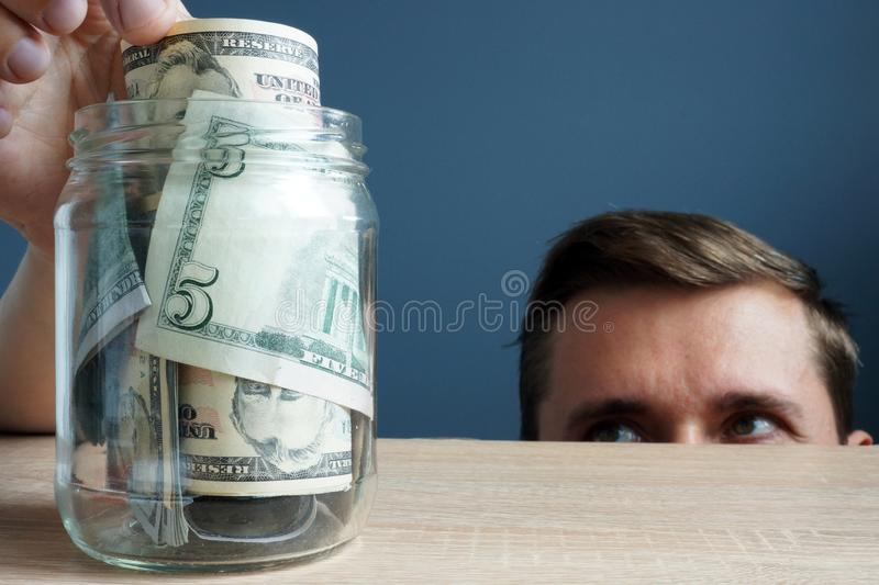 Man takes out the banknote from jar. Financial infidelity concept. royalty free stock image