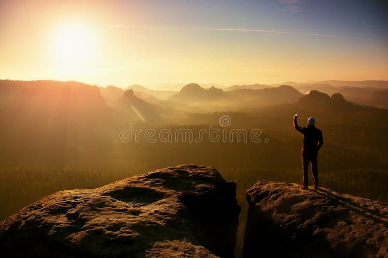 Man takes photos with smart phone on peak of rock empire. Dreamy fogy landscape, spring orange pink misty sunrise in a beautiful v stock photos