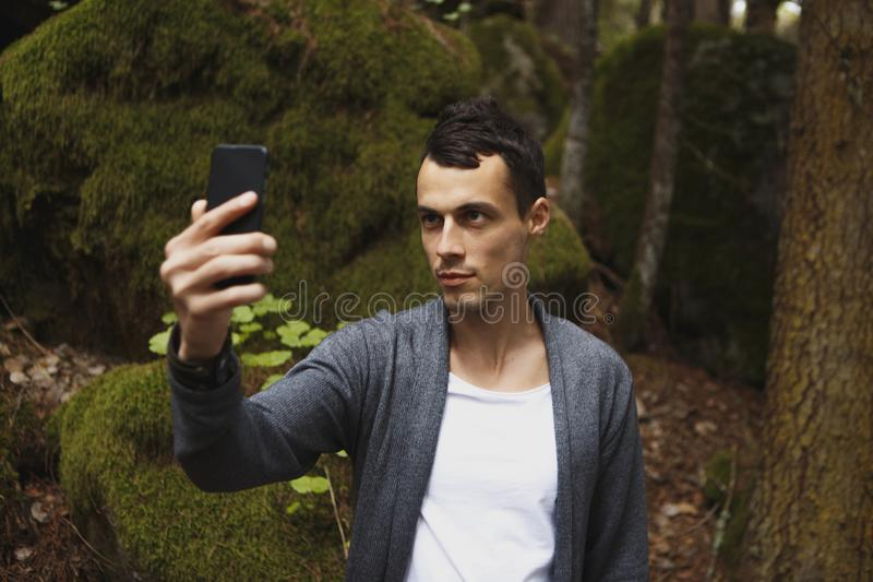 Man takes a picture on mobile phone in the pine forest on a cold sammer day stock photo