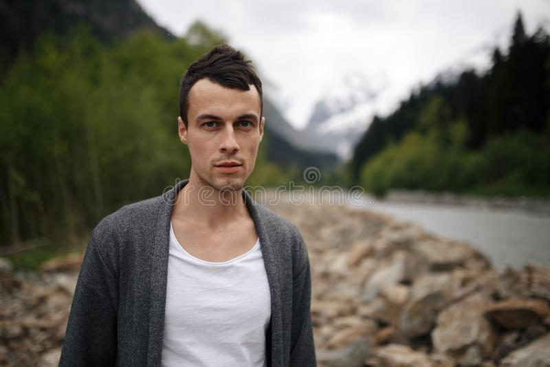 Man takes a picture on mobile phone in the pine forest on a cold sammer day royalty free stock photo