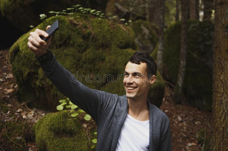 Man takes a picture on mobile phone in the pine forest on a cold sammer day royalty free stock image