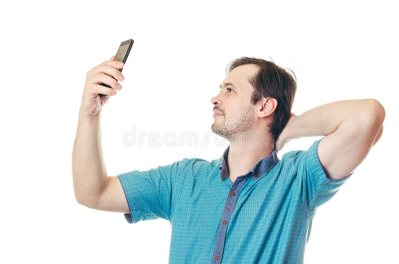 The man takes a selfie phone. The man with a beard on cheeks in blue to a shirt takes a selfie phone and smiles royalty free stock photos