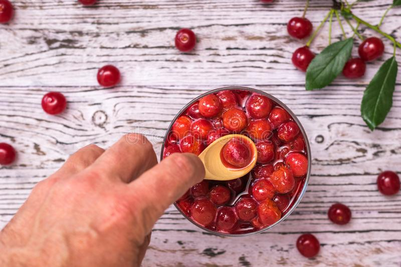 A man takes a wooden spoon cherry berry from a bowl of jam. Homemade jam from the fresh harvest of cherry berries. Flat lay. A man takes a wooden spoon cherry royalty free stock photo