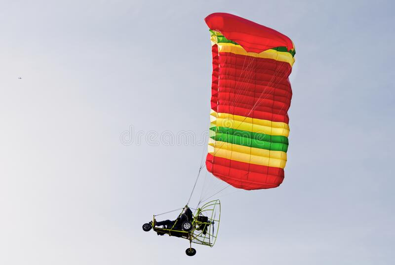 Motorized paraglider in flight riding towards the sun. Man taking an adventure in his motorized paraglider flying towards the sun royalty free stock photography
