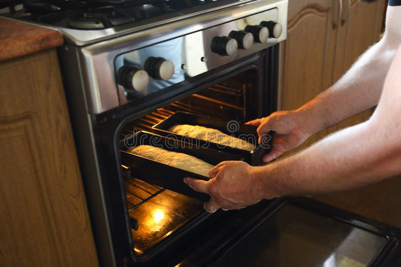 Man taking baked loafs of bread out of the oven. Beaking bread at home stock photo