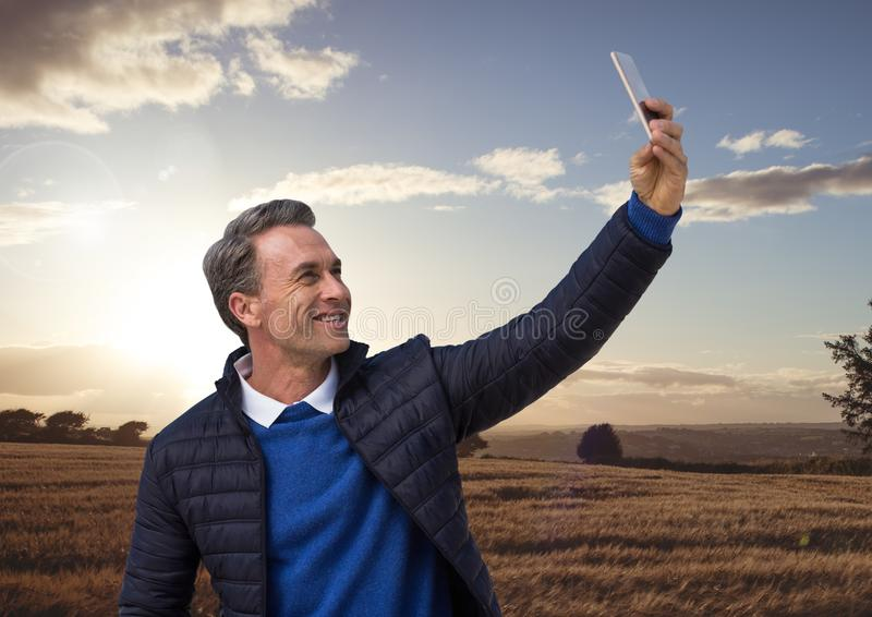 Man taking casual selfie photo in front of farm field landscape. Digital composite of Man taking casual selfie photo in front of farm field landscape royalty free stock photography