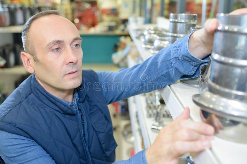 Man taking flue adaptor from shelf in store. Chimney stock images