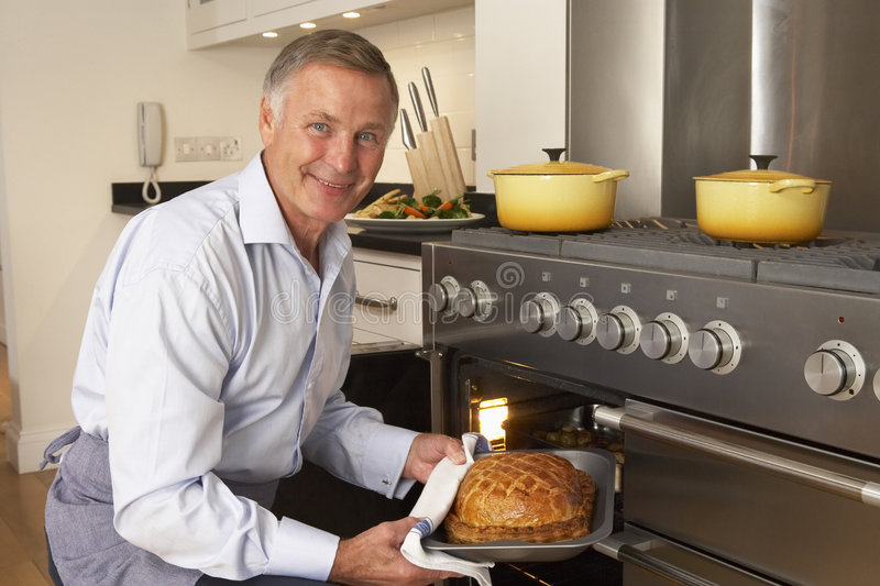 Man Taking Food Out Of The Oven stock image