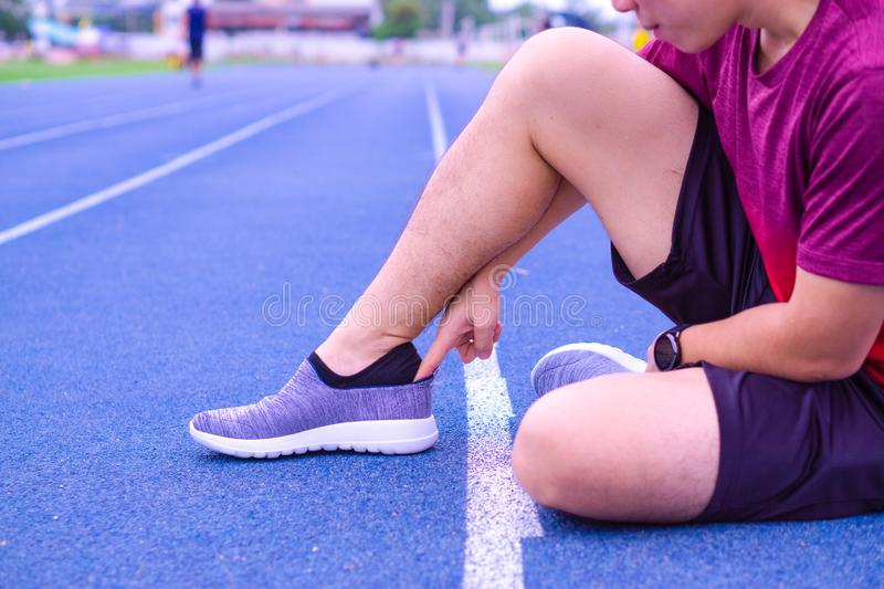 A man is taking on grey sports shoes on the running track. Sport and exercise concept stock photography