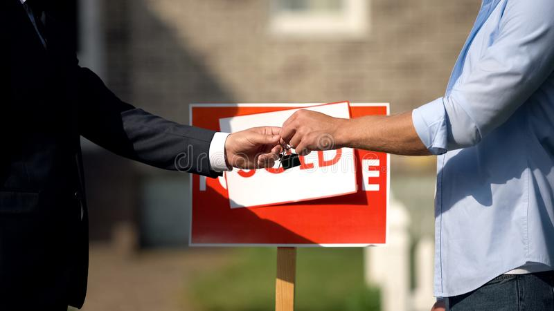 Man taking house keys from estate agent, successful deal, property purchase sale. Stock photo royalty free stock images