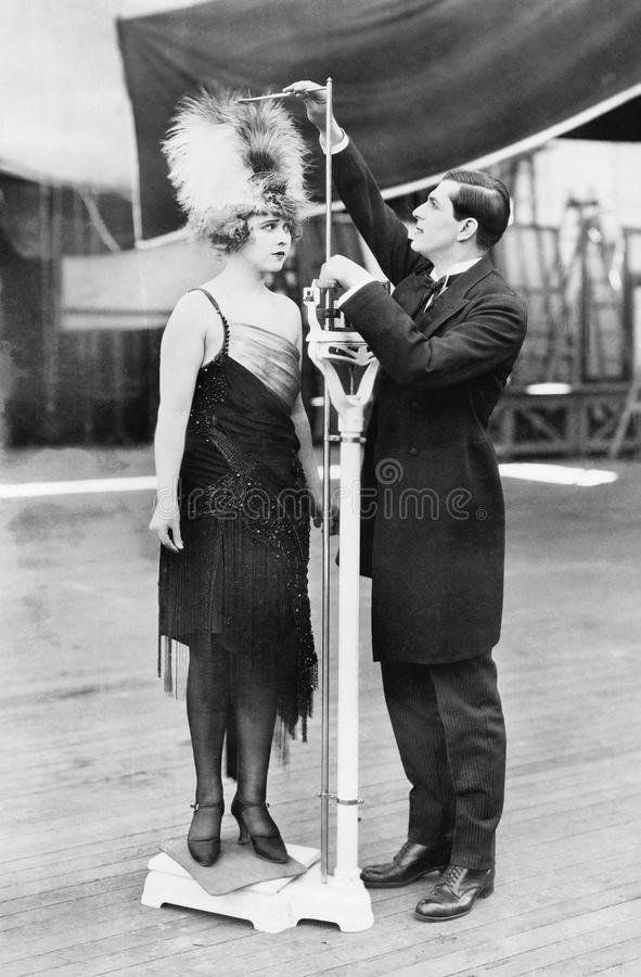 Man taking a measurement of a woman with an oversized hat royalty free stock images