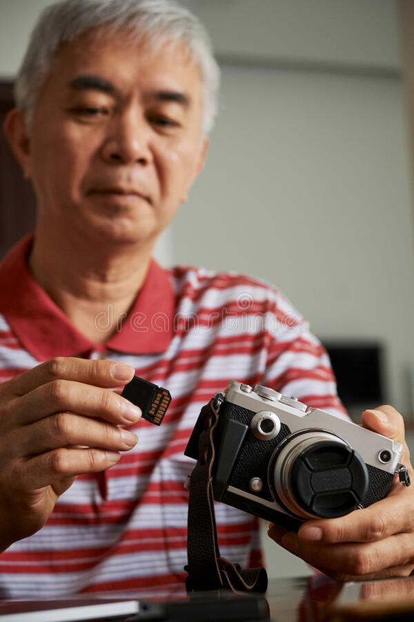 Man taking memory card out of camera stock photography