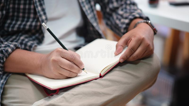 Close-up view of man taking notes stock photo