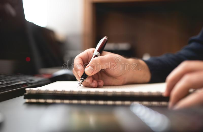Man Taking Notes on Notebook and Doing Plans on Work Desk stock photography