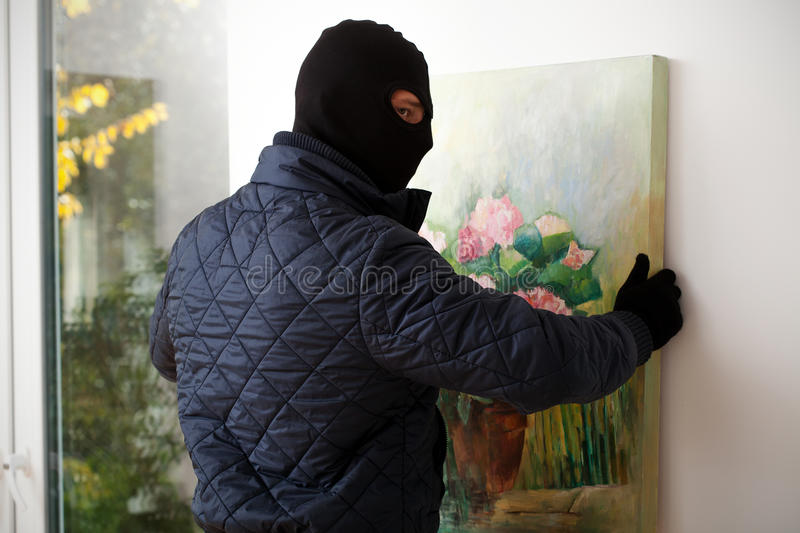 Man taking off painting. A masked man trying to take a painting off the wall royalty free stock image