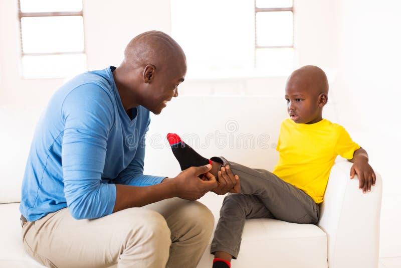 Man taking off son's socks. Loving african men taking off son's socks royalty free stock photo