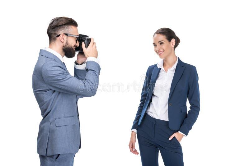 Man taking photo of beautiful smiling businesswoman,. Isolated on white stock image
