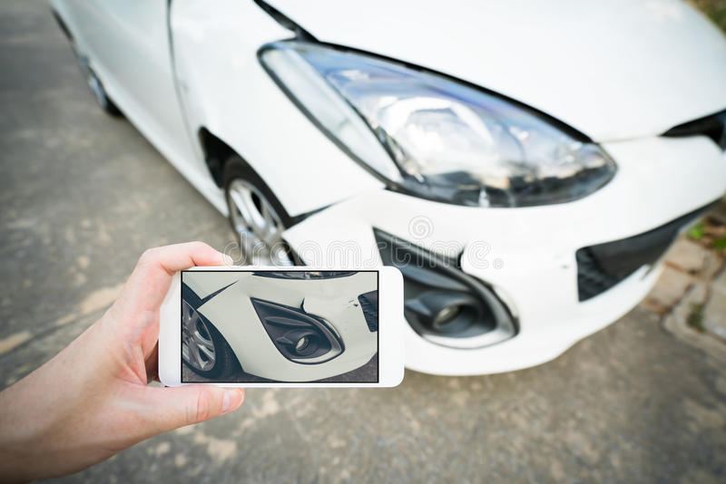Man taking photo of damaged white car with smartphone royalty free stock images